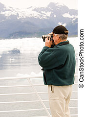 Filming Alaska - Senior citizen with videocamera at Alaskan...