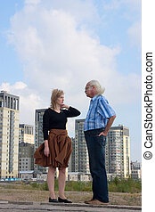 Couple talking - Couple standing against cityscape and...