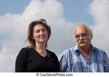 Couple standing together against cloudy sky