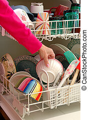 Washing Dishes - A female hand is shown loading dishes into...
