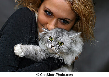 Portrait with a cat - The beautiful girl embraces a kitten