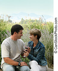 Celebrating outdoor - Young couple having picnic with wine