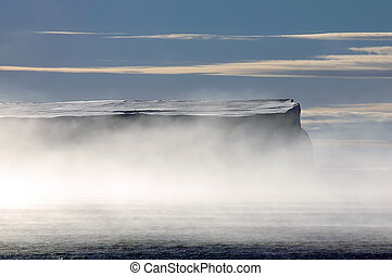 Antarctic table iceberg in morning mists - A large frontlit...