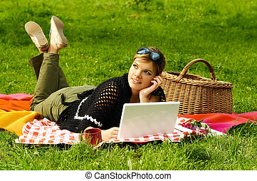 Busy Picnic - Young business woman working on laptop...