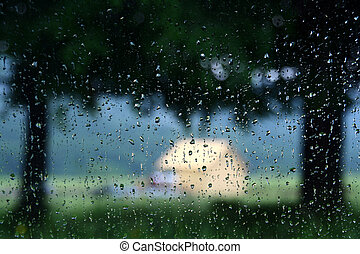 Rain drops on window glass with blurry view behind