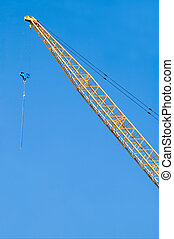 Construction Crane - Idle construction crane against a blue...