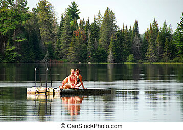 Family fun lake - Grandmother and granddaughter sitting on a...