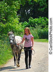 Girl walk pony - Young girl walking with a pony on a farm...