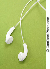 White headphones with a green background. concept of music