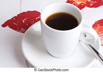 Coffee cup on a flower tablecloth