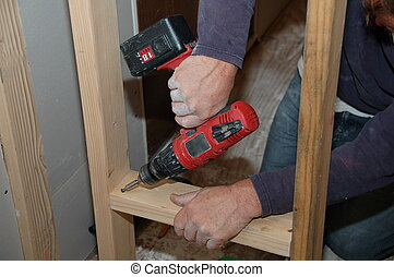Contractor at Work - contractor using drill when framing new...