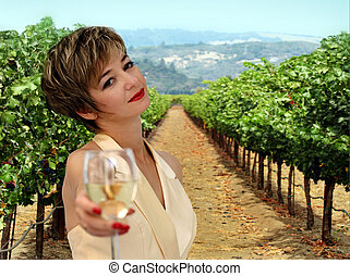 woman at vineyard - Beautiful woman offering a glass of...