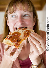 Woman Eating Pepperoni Pizza - Photo of a woman eating...