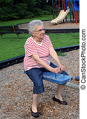 Seesaw Grandma - Senior citizen woman on a playground seesaw...