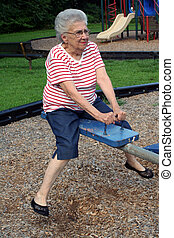 Seesaw Grandma 2 - Senior citizen woman on a playground...