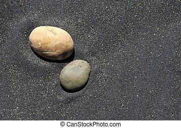 stone and sand - stones on black sand at Patea, Taranaki,...