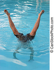 Man does a handstand in a swimming pool