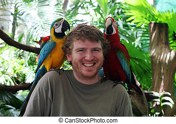 Jungle friends - Tourist with parrots on his shoulders