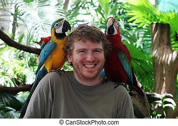 Jungle friends - Tourist with parrots on his shoulders