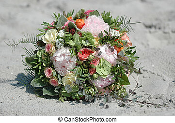 Wedding bouquet in the sand. The bouquet contains mostly...