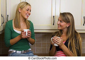 Girl Talk - Two beautiful young women drinking and chatting...