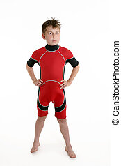 Child wearing a wetsuit - A young boy standing wearing a red...