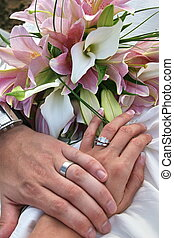 wedding rings - bride and groom holding hands showing rings