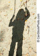 shadow of a girl on a swing at playground