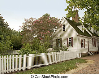 Picket Fence Home - A small old colonial home with a white...