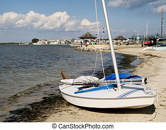 Sailboat On Shore - A small sailboat on the shore of a bay.