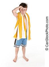 Beach boy - Boy in board shorts and beach towel slung over...