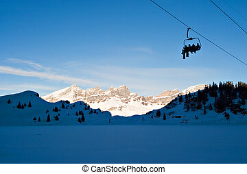 Ski Lift - Skiers on Ski Lift, on the Swiss Alps.