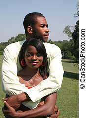 Couple hug - An African American couple outside in a park....