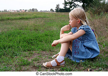 Resting - Little girl resting in the meadow and eating