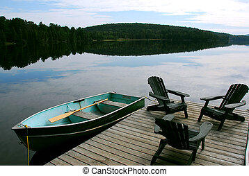 Lake chairs - Three wooden adirondack chairs on a boat dock...