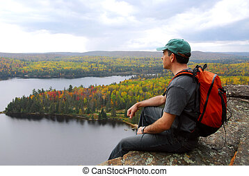 Hiker - A hiker sitting on a cliff edge enjoying scenic view