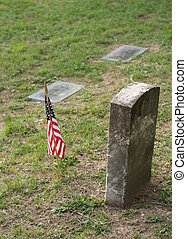 Tombstone and US Flag - A tombstone or grave marker with an...