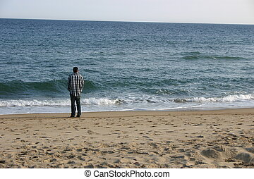 Man at ocean - A man looking out at the ocean and waves.