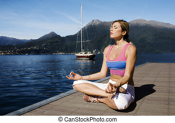 yoga - blond girl doing yoga nearby the lake