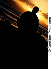 Sunset Sitter - Human figure sitting on the shore at sunset