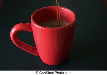 fresh perked - coffee being poured into red mug on black...