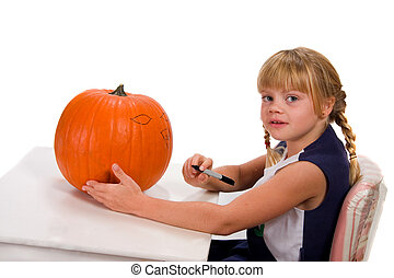 Pumpkin Carving - Young girl drawing on pumpkin for carving