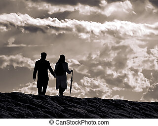 young couple walking on the stormy sky background along...