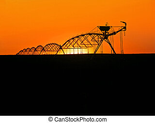 Water Sprinklers - Water sprinklers silhouetted in prarie...