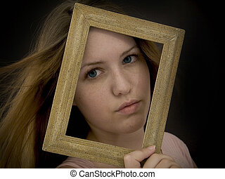 framed - Woman holding an old picture frame over her face.