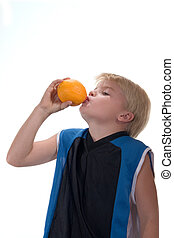 Fresh squeezed - Young boy drinking fresh juice from an...