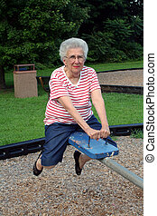 Seesaw Grandma 5 - Senior citizen woman on playground seesaw...