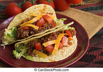 mexican tacos with lettuce ,cheese and beef