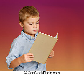 Young Boy Reading - Young boy reading a book against plain...