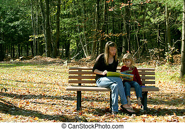 Quality Time - Mother and daughter sitting on bench outdoors...
